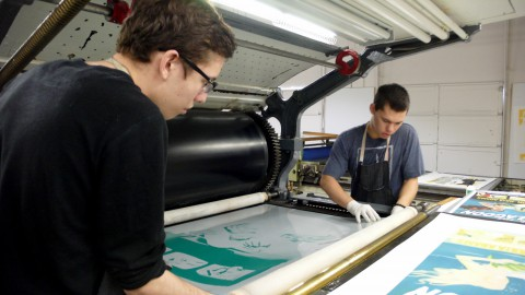 Foreground: Roman Gonzales, Background: Cameron Woodward, producing a lithograph on a French Marinoni Voirin press.